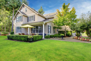 A beautiful home with a lush lawn features tan vinyl siding, a shingle roof, and a large patio.