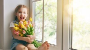 A laughing child sits on the sill of a large window holding a bundle of tulips.